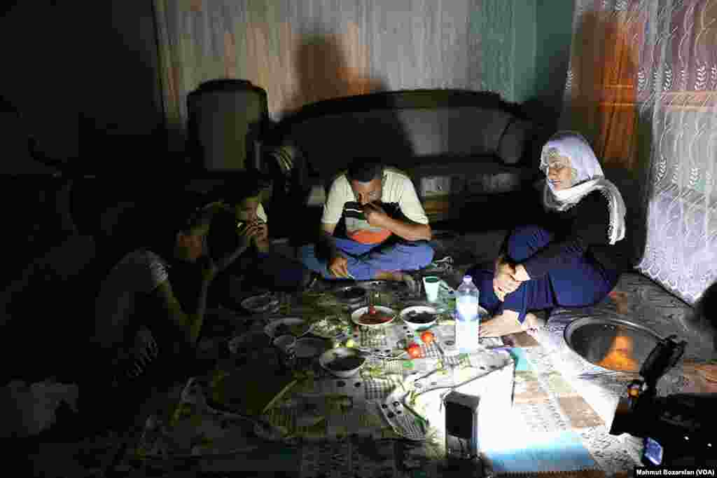 The government has cut power and water to Sur, in Diyarbakir, Turkey, as efforts are made to rebuild it. A family eats by the light of a lantern in their home.