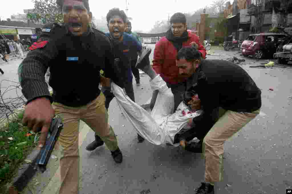 Pakistani police officers and volunteers rush an injured man to a hospital after a bombing in Lahore, Pakistan, Feb. 17, 2015.