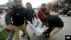2015年2月17日巴基斯坦拉合尔: 爆炸后巴基斯坦警察和志愿者将受伤男子送往医院