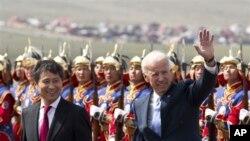 ຮອງປະທານາທິບໍດີສະຫະລັດ ທ່ານ Joe Biden ໂບກມືໃຫ້ພວກທີ່ມາຕ້ອນຮັບ ຂະນະທີ່ຍ່າງຢູ່ຄຽງຂ້າງ ນາຍົກລັດຖະມົນຕີມົງໂກເລຍ ທ່ານ Batbold Sukhbaatar ທີ່ໄປຕ້ອນຮັບທ່ານຢູ່ເດິ່ນບິນສາກົນ Chinggis Khaan ໃນນະຄອນຫລວງ Ulan Bator ຂອງມົງໂກເລຍ, ວັນຈັນ ທີ 22 ສິງຫາ 2011. (AP Photo/Andy