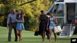 De izquierda a derecha, el presidente Obama, su hija Malia, la primera dama Michelle y su otra hija, Sasha, regresan de sus vacaciones en Martha's Vineyard, Massachusetts.