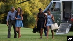 FILE - From left, President Barack Obama with daughter Malia and first lady Michelle Obama with daughter Sasha, walk form Marine One across the South Lawn of the White House in Washington, Aug. 23, 2015.