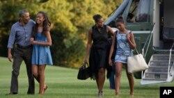 ປະທານາທິບໍດີ Obama ພ້ອມດ້ວຍລູກສາວ ນາງ Malia ແລະສະຕີໝາຍເລກນຶ່ງ ທ່ານນາງ Michelle Obama ກັບລູກສາວ ນາງ Sasha.