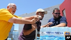Leo Block, left, Matari Phason, center, and Brian Juarez push part of a shipment of 20,000 bottles of water donated by Yellow Cab of Phoenix to a local homeless shelter to help prepare for the summer heat in Phoenix, June 14, 2016.