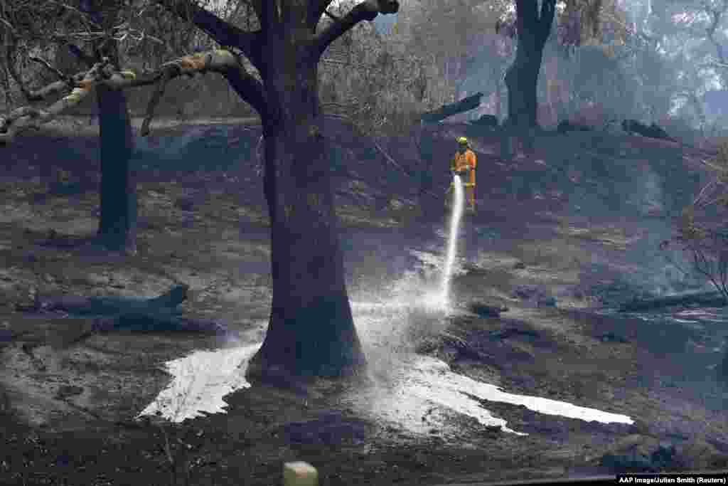 A CFA firefighter sprays water after a fire impacted Clovemont Way, Bundoora in Melbourne, Australia.