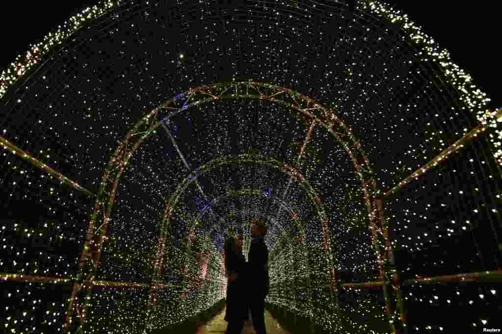 Sepasang muda-mudi menikmati instalasi lampu-lampu gemerlap di Kew Gardens, London.