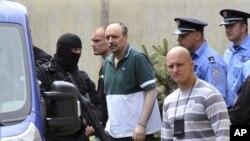 塞尔维亚警察7月22日在哈季奇(中,穿绿衣者)看望了他病重的母亲后,押解他离开