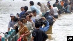 물에잠긴 다리를 건너 대피하는 수재민들(자료사진)