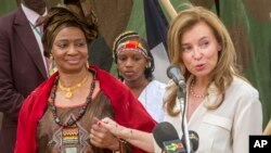 Ibu negara Perancis Valerie Trierweiler (kanan) didampingi ibu negara Mali, Mintou Doucoure, menjawab pertanyaan media di Gao, Mali (16/5). Valerie Trierweiler mengadakan kunjungan selama dua hari di negara yang dilanda perang ini sebagai bagian dari misi mengangkat peran tentara perempuan (AP Photo/Olivier Debes, ECPAD).
