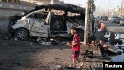 Seorang anak laki-laki berdiri di dekat sebuah mobil yang meledak di Sadr City, dekat Baghdad (28/10).
