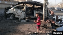 A boy stands at the site of a car bomb explosion in Sadr City, northeastern Baghdad, October 28, 2012.