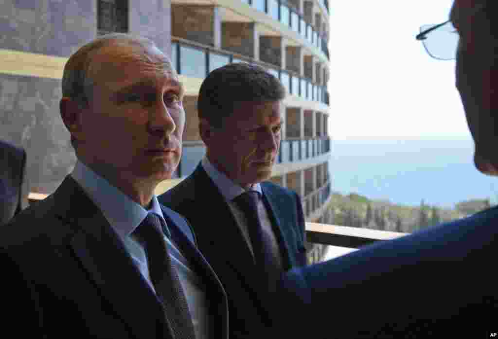 President Vladimir Putin, left, listens to Sberbank President German Gref (right) in Yalta , Crimea, Aug. 14, 2014.