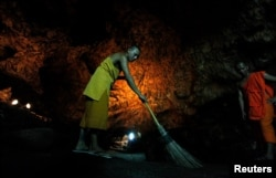 FILE - A Buddhist monk sweeps up bat guano in a cave near Wat Khao Chong Phran Temple in Ratchaburi province, Thailand, September 14, 2009.