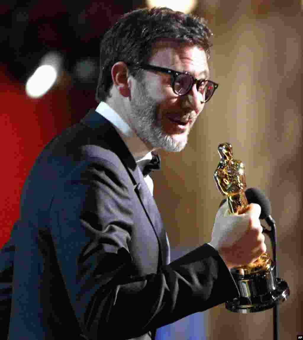 """Режисерот Мешел Ханзанавишус ја прифаќа наградата за најдобра режија за """"Артист"""". (AP)"""