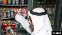 Warga Kuwait Abu Yousif membeli sekaleng bir non-alkohol dari sebuah toko kelontong kecil di pusat kota Kuwait pada 20 April. (Foto: Reuters)