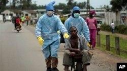 Zdravstveni radnici prevoze čoveka, zaraženog ebolom, u Liberiji