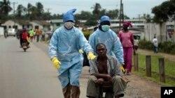 Les habitants du quartier Saint-Paul Pont couverts d'un équipement de protection individuelle transportent un homme soupçonné de porter le virus Ebola à la Clinique île à Monrovia, au Libéria, le dimanche 28 septembre 2014.Six months into the world's worst-ever Ebola outbreak, a