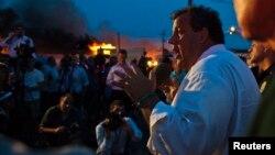 Gubernur New Jersey Chris Christie berbicara kepada media sementara regu pemadam kebakaran berusaha memadamkan api di Seaside Park, 12/9/2013.