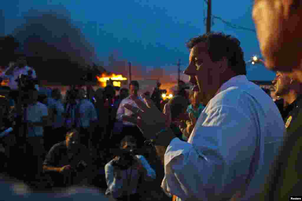 New Jersey Governor Chris Christie speaks with the media while firefighters work to control a massive fire in Seaside Park, Sept. 12, 2013.