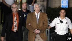 Mantan pelatih sepakbola Amerika, Jerry Sandusky (tengah) dikawal pihak berwajib meninggalkan pengadilan setelah divonis bersalah terkait pelecehan seks di Bellefonte, Philadelphia (22/6).