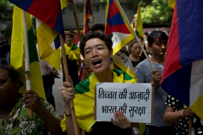 FILE - Exile Tibetans shout slogans during a protest to show support with India on Doklam standoff in New Delhi, India, Aug. 11, 2017.