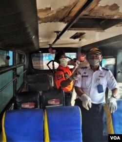 Para petugas melakukan penyemprotan disinfektan di dalam sebuah bus (VOA/Yudha).