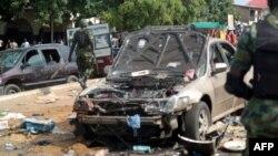 Các sĩ quan quân đội đi qua hiện trường vụ nổ ở Kaduna, miền bắc Nigeria 23/7/2014.