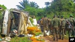 Des soldats des Forces de défense congolaises inspectent les lieux d'une attaque près de la ville d'Oicha, à 30 km de Beni, en République démocratique du Congo, le 23 juillet 2021.