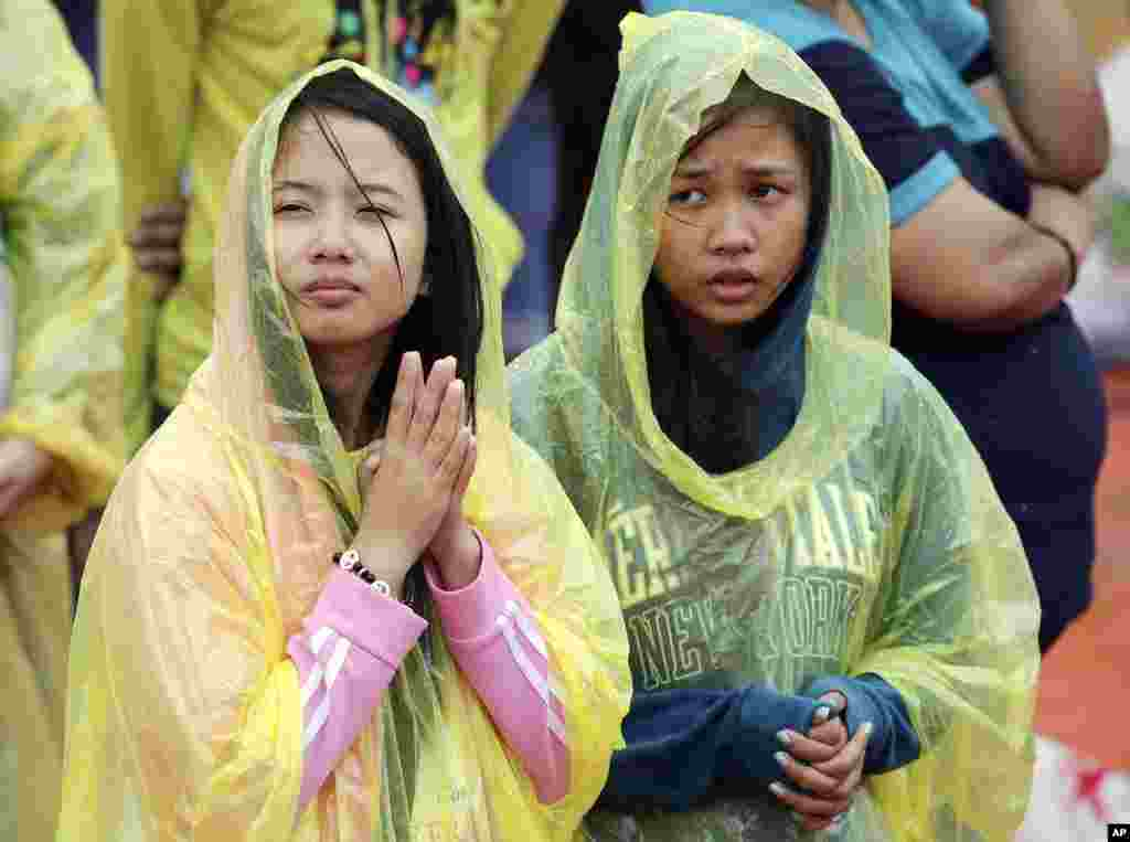 Young Filipino women pray during the visit of Pope Francis at the University of Santo Tomas in Manila, Jan. 18, 2015.