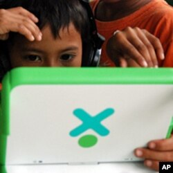 A child at a Phnom Penh orphanage focuses on playing the computer game, which requires him to find food in the Cambodian countryside while avoiding on-screen landmines, June 2010
