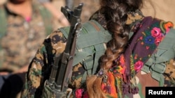 FILE - A Syrian Democratic Forces (SDF) female fighter's braid is pictured while she is carrying her weapon in Tal Samin village, north of Raqqa city, Syria, Nov. 19, 2016. The Syrian government has created an all-female military unit in a predominantly Kurdish city in northeastern Syria.