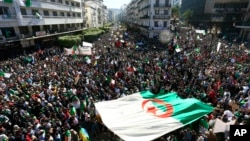 Algerians march with a giant national flag during a protest in Algiers, Algeria, March 15, 2019. Tens of thousands of people gathered Friday in Algeria's capital and other cities for what could be decisive protests against longtime leader Abdelaziz Bouteflika.