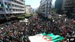 Les Algériens exhibent un drapeau national géant lors d'une manifestation à Alger, le 15 mars 2019.