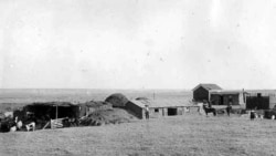 An 1889 photo of a sod home and farm built by settlers in Kansas