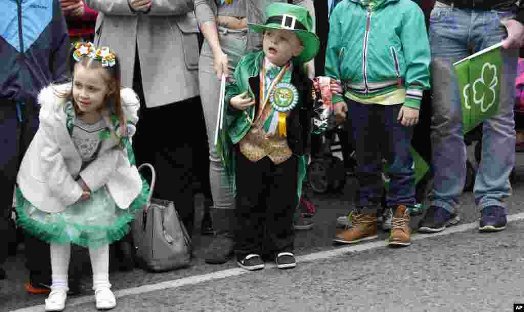 Anak-anak menunggu parade Hari St Patrick di tengah kota Belfast, Irlandia Utara, 17 Maret 2015.