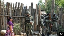 Mexican army soldiers stand outside a home where gunmen killed an elderly woman and two of her grandchildren in the Pacific resort city of Acapulco, March 15, 2011