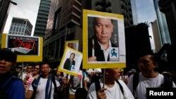 香港抗议者举着人权律师浦志强和记者高瑜的头像 (2014年7月1日 资料照片)