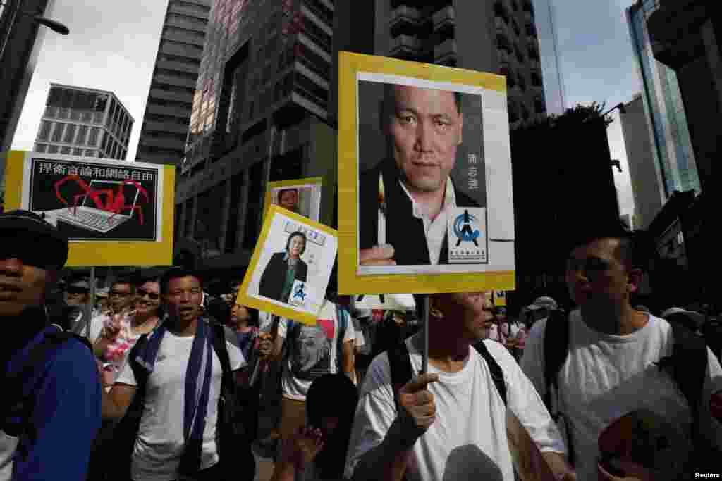 Protesters carry portraits of detained Chinese human rights lawyer Pu Zhiqiang (right) and mainland journalist Gao Yu as they join tens of thousands of others during a march to demand universal suffrage, Hong Kong July 1, 2014.