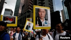 2014年7月1日抗议者举着中国维权律师浦志强(右)和大陆记者高瑜的画像游行