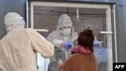 Seorang anggota staf medis yang mengenakan alat pelindung mengambil sampel dari seorang pengunjung untuk menguji virus corona Covid-19 di stasiun pengujian sementara di luar stasiun kereta api di Seoul pada 16 Desember 2020. (Foto: AFP)