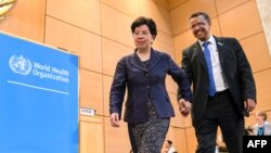 Outgoing Director-general of the World Health Organization (WHO), China's Margaret Chan (L), leads new WHO Director-general, Ethiopia's Tedros Adhanom Ghebreyesus, to the podium after his election during the World Health Assembly (WHA) in Geneva, Switzerland, May 23, 2017.