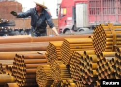 An employee unloads steel products at a market in Yichang, Hubei Province, China, April 11, 2016.
