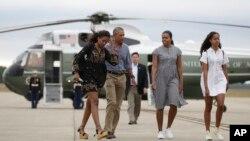 바락 오바마(왼쪽 두번째) 대통령과 부인 미셸(세번째) 여사, 딸 말리아(오른쪽)와 사샤가 21일 메사추세츠주의 휴가지를 떠나기 위해 헬기 편으로 케이프 코드 해안경비대 항공기지에 도착, 공군 1호기로 갈아타기 위해 활주로를 걷고있다.