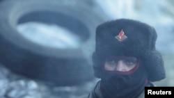 2014年1月30日,在乌克兰首都基辅反政府群众和防暴警察发生冲突,一名反政府示威分子站在旁边观看。