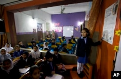 A student shares information with her classmates regarding awareness about rape and kidnap attempts at a school in Kasur, Jan. 19, 2018.