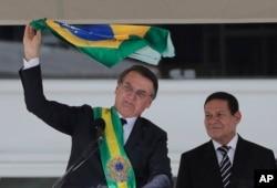 Brazil's President Jair Bolsonaro, flanked by his Vice President Hamilton Mourao, waves the national flag from the Planalto Presidential palace, in Brasilia, Brazil, Jan. 1, 2019.