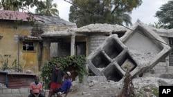 图为海地居民两年今年1月3日坐在两年前被震坏的房屋前。