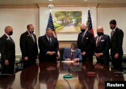 Republican Governor Brian Kemp signs the law S.B. 202, a restrictive voting law that activists have said aimed to curtail the influence of Black voters who were instrumental in state elections that helped Democrats win the White House