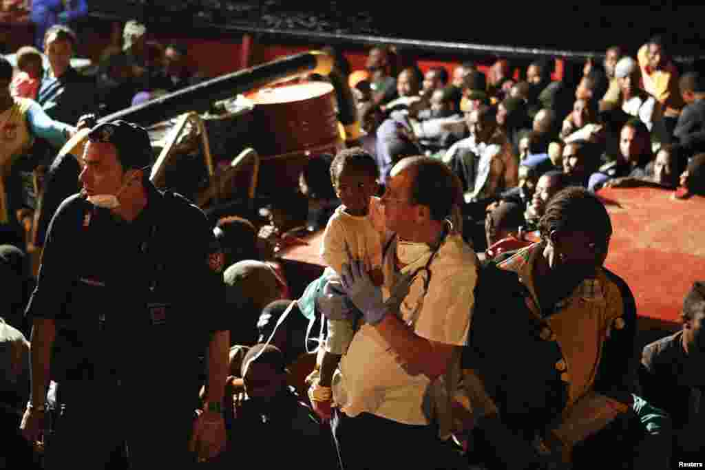 Migrants arrive by rescue boat with a group that includes Syrian refugees, Pozzallo harbor, Sicily, Sept. 17, 2013.