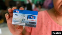 Seorang perempuan memegang kartu SIM yang ia menangkan dalam sebuah lotere di Rangoon, Burma (24/6). (Reuters/Soe Zeya Tun)